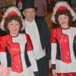 Heinz Schulte wird in Begleitung zweier Funkenmariechen zur RENI-Ordensverleihung auf die Bühne begleitet.
